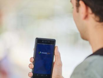 Photo of a person looking at a smartphone held in their hand to load the MyTransLink app loads